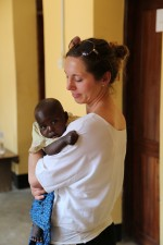Laura holding a patient's baby whilst she gets a contraceptive implant (2)